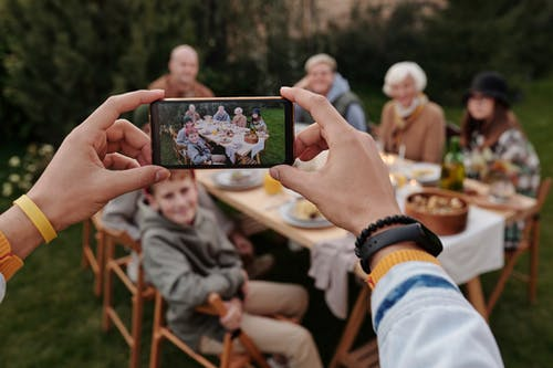 Unrecognizable person taking photo of family dinner on smartphone