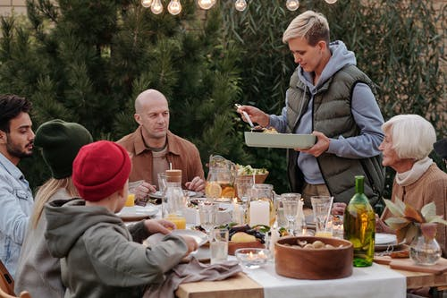 Multigenerational family in warm clothes enjoying celebration dinner together outdoors