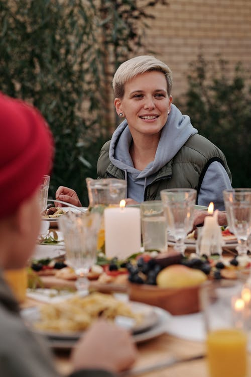 Cheerful hipster woman enjoying delicious dinner together with friends