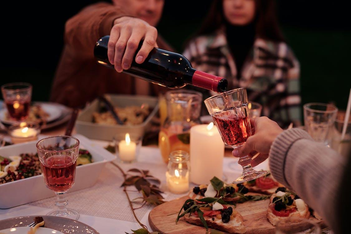 Erntemann Gießt Wein Zu Leuten Auf Familienessen