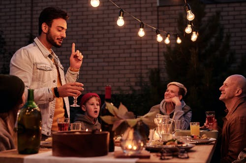 Ethnic guy offering toast at dinner with friends