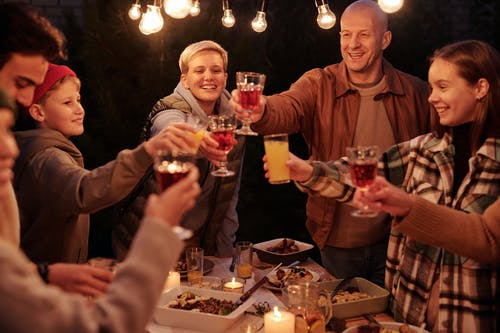 Laughing friends with kids spending time in backyard at night enjoying dinner with garlands and clinking glasses