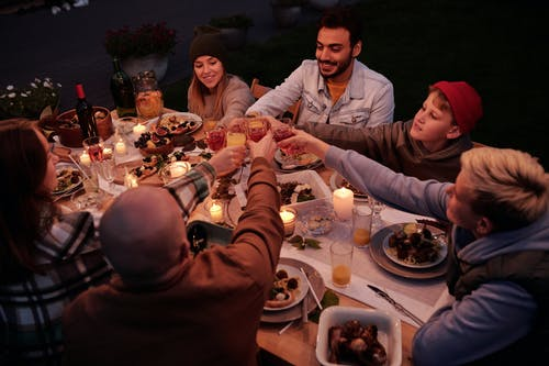 From above multiethnic people with children spending evening at dinner in dusky garden and cheering with drinks