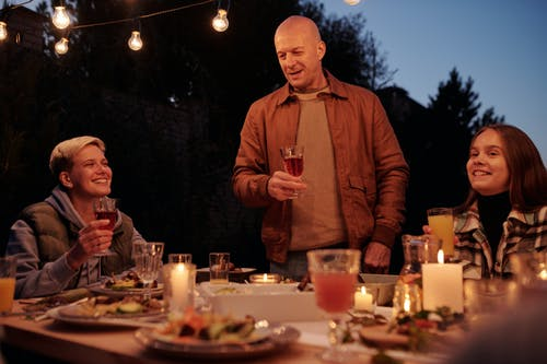 Adult man with wineglass offering toast while standing at table with family and friends in backyard in twilight