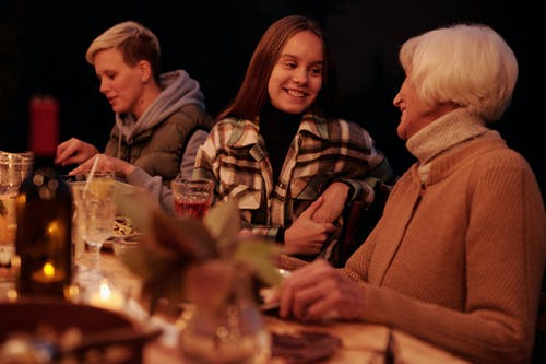 Smiling girl with grandmother talking at table in backyard having family reunion dinner in evening