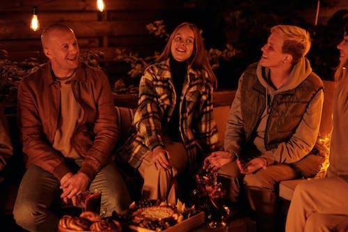 Laughing friends around bonfire in night garden
