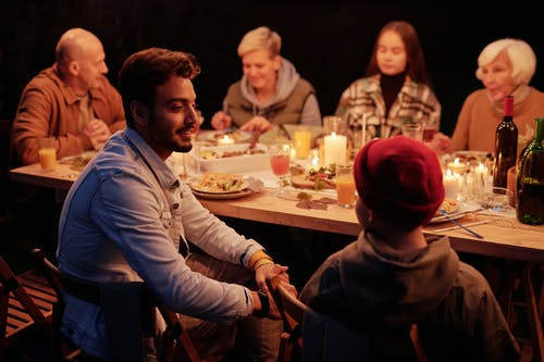 Smiling Indian man and boy chatting at festive table with family and friends during reunion