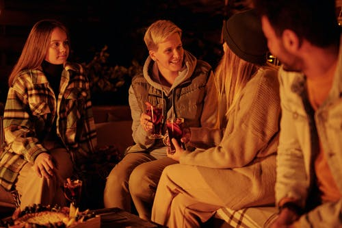 Cheerful friends with mulled wine at bonfire in garden