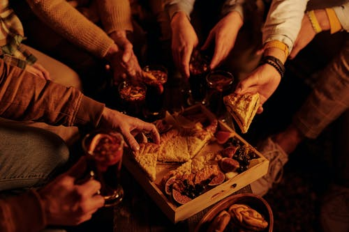 From above faceless people sharing delicious pie with sweet snacks and mulled wine enjoying night in garden