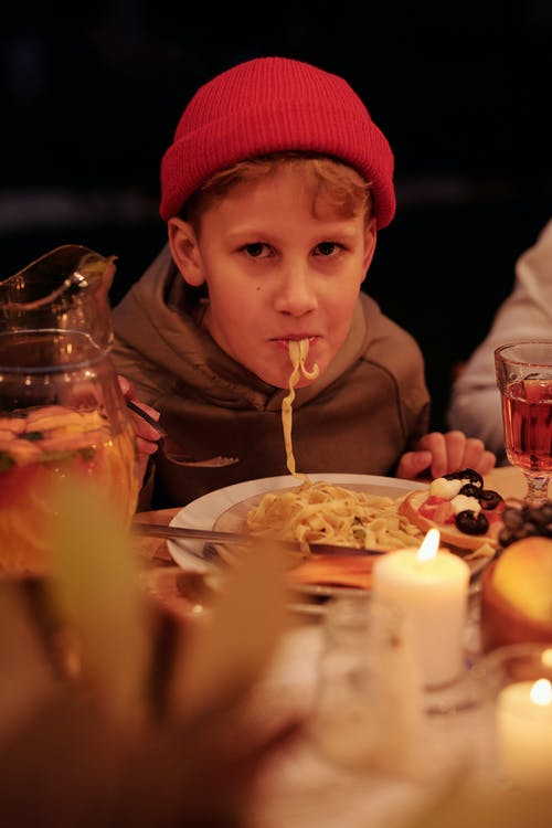 Content kid in beanie enjoying delicious pasta sitting at table in evening garden during holiday dinner