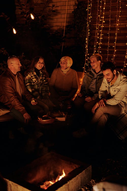 Family gathering around bonfire in dark backyard