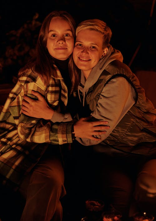 Positive female friends wearing warm clothes hugging and looking at camera while sitting  near campfire in nature at evening time