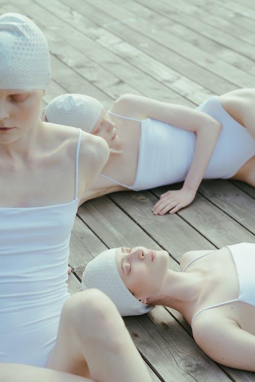 Women Wearing White Swimwear Lying on a Wooden Floor