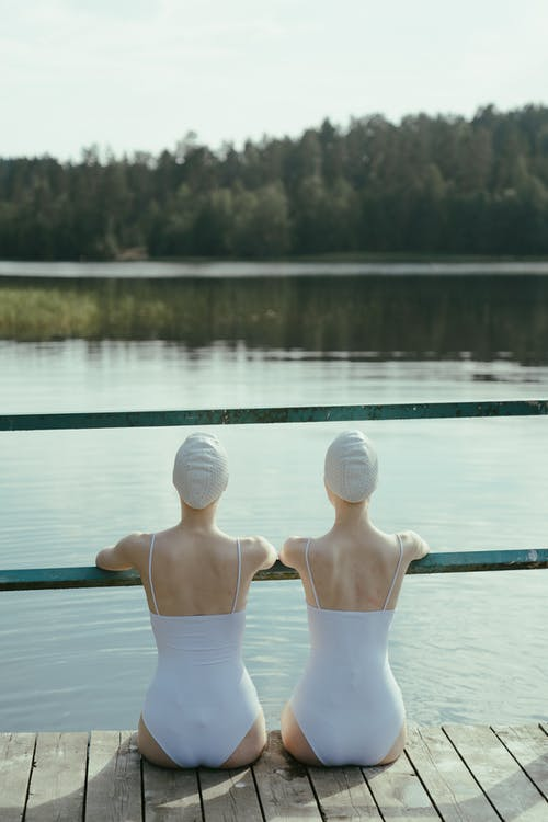 Two Persons in White Swimsuits Sitting on the Dock