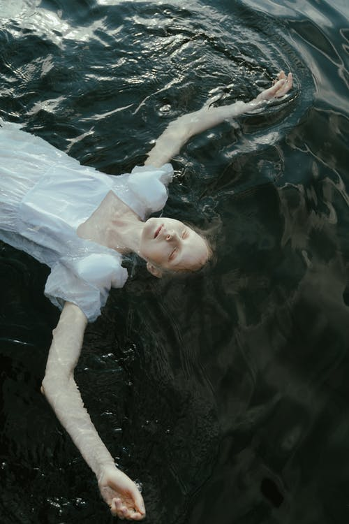 Girl in White Dress Floating on Water