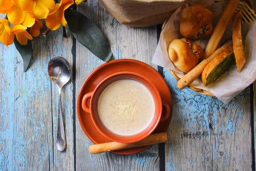 Basket of Bread and Creamy Soup on Wooden Table Top