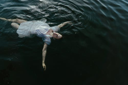 Woman in White Dress Floating on Water
