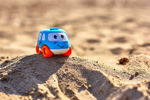 Blue and White Toy Car on Beach Sand