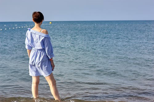Woman in Blue Dress Standing in the Beach