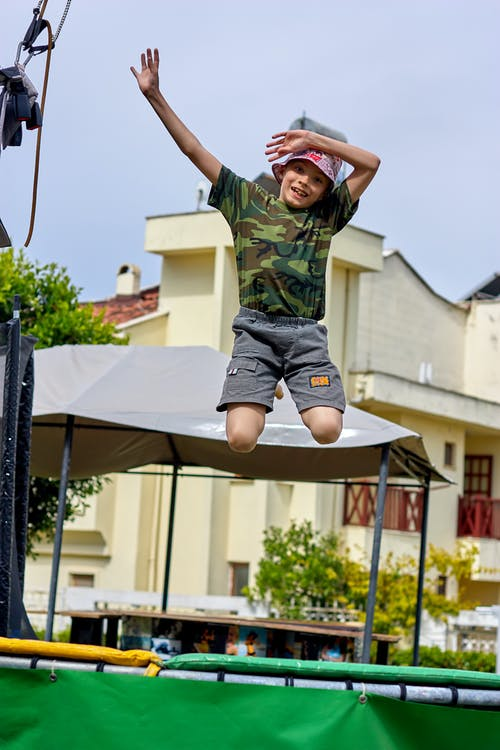 A Kid in Camouflage T-shirt Jumping on a Trampoline