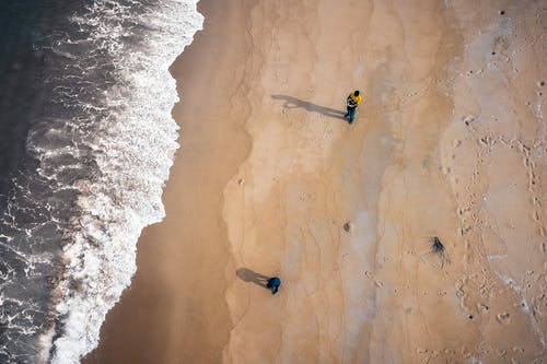 From above sea waves and vast sand shore with people and footprints at daytime