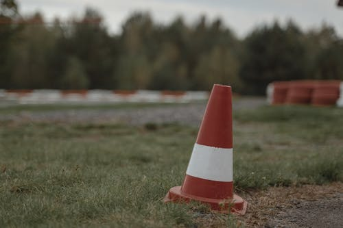 Orange and White Traffic Cone on Green Grass Field