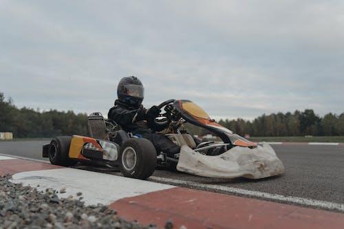 Person Riding Orange and Black Go Kart