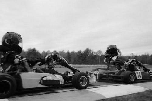 Grayscale Photo of Man Riding on Go Kart