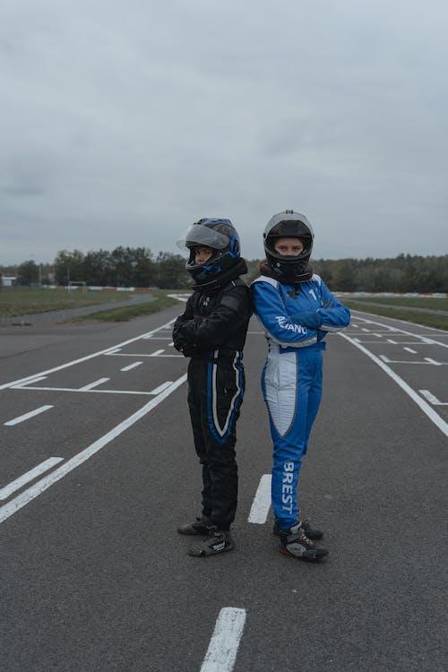 Man in Blue Jacket and Blue Pants Wearing Black Helmet Standing on Road