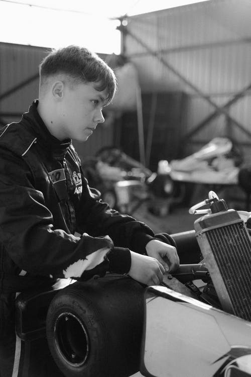 Grayscale Photo of Boy in Black Jacket Playing Piano