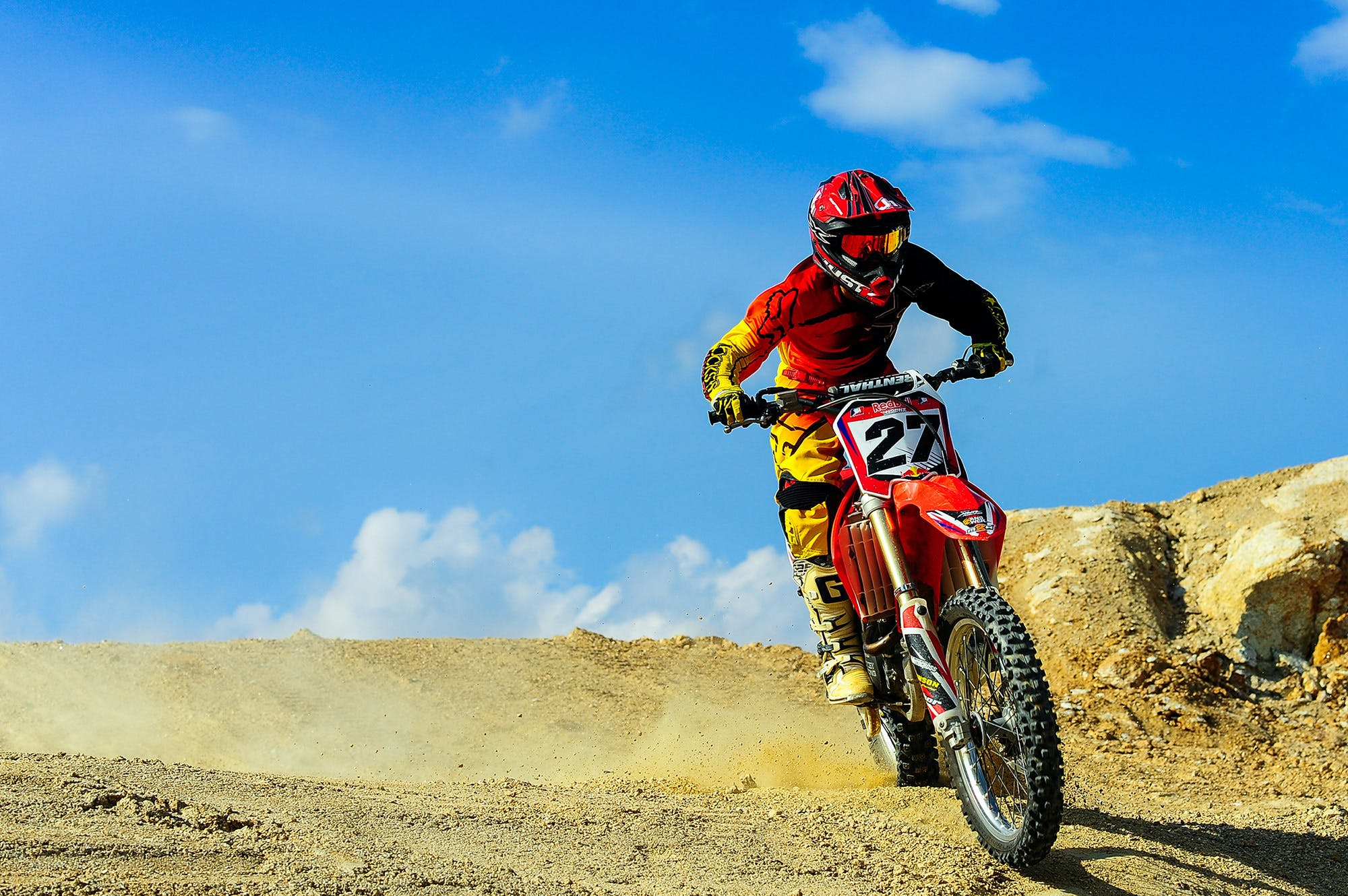 Person Driving Motocross Dirt Bike Under Blue Sky