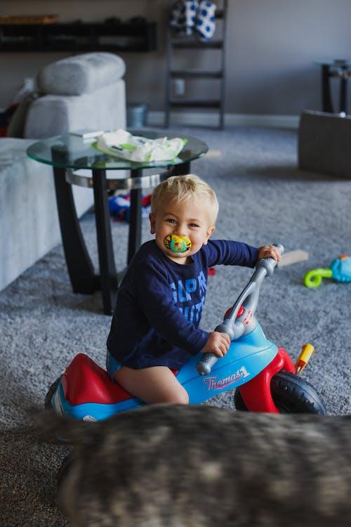 Cute boy on walker car at home