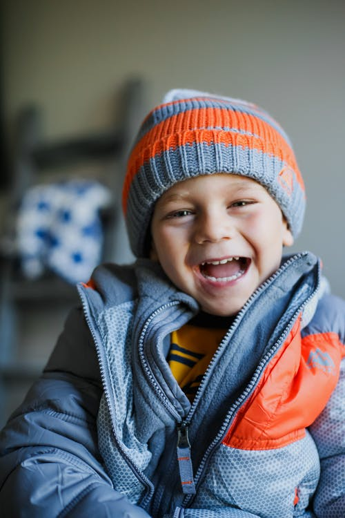 Cheerful kid in warm hat and jacket laughing at camera standing in living room