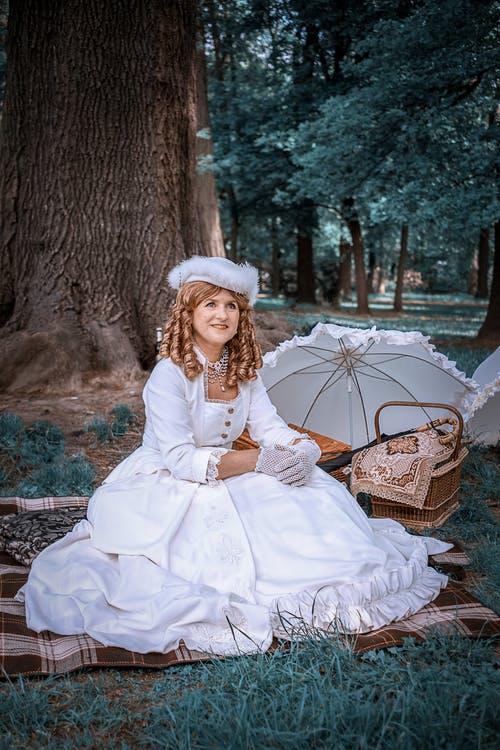 Woman in White Dress Sitting on Brown Wooden Bench