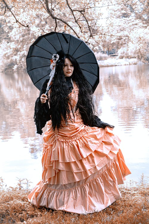Woman in Orange Dress Holding Umbrella
