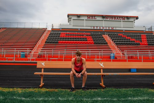 Full length focused young man sitting on bench on football field against stadium looking at camera