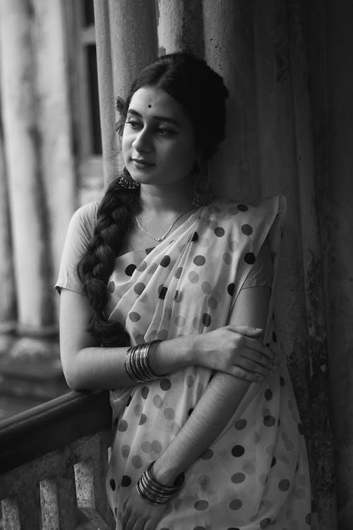 Dreamy Asian woman in sari and bindi touching arms
