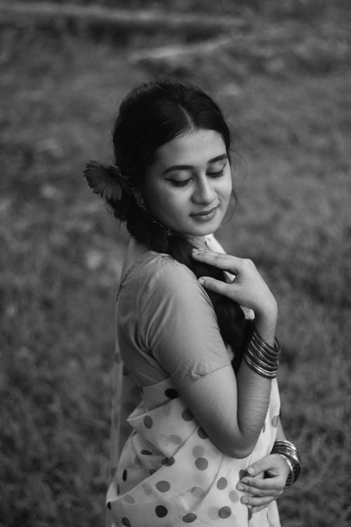 From above black and white of young female with flower in hair wearing sari and bracelets touching braid on blurred grass background