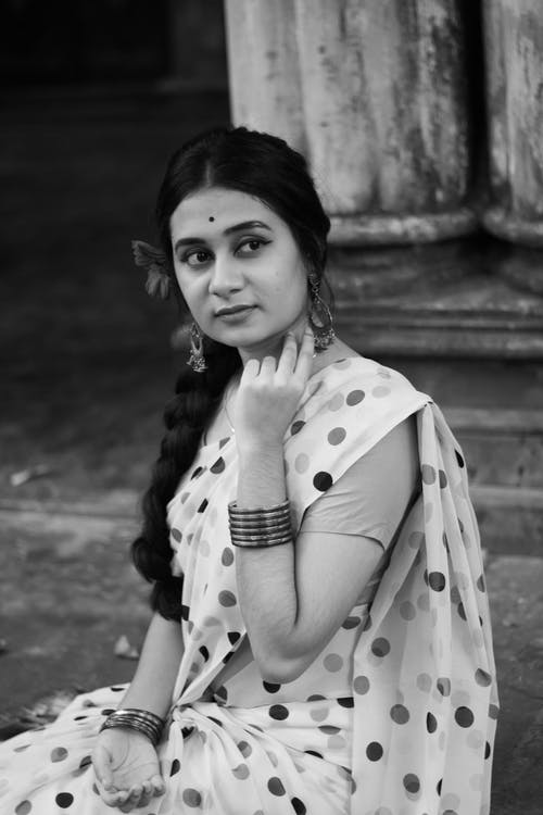 From above black and white of long haired young Indian woman with jewelry and bindi on forehead looking away while sitting on street