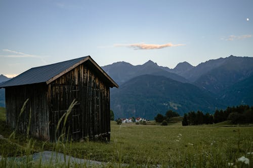 Old lumber hut in green valley with grass and high hills covered with forest
