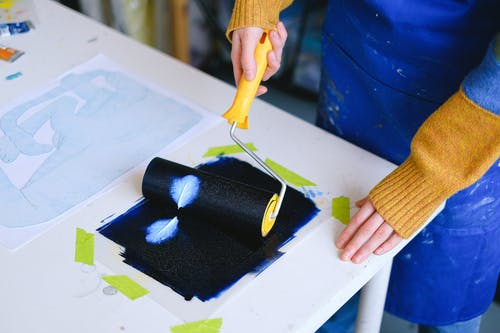 Unrecognizable painter creating artwork with roller on paper