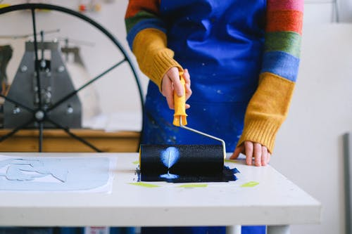 Unrecognizable painter creating artwork on paper with roller