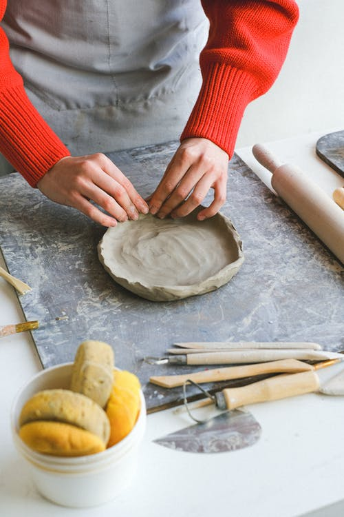 Crop faceless lady in apron standing near table while shaping piece of clay with hands near sponges and double end loops with stacks and rolling pin for pottery in studio