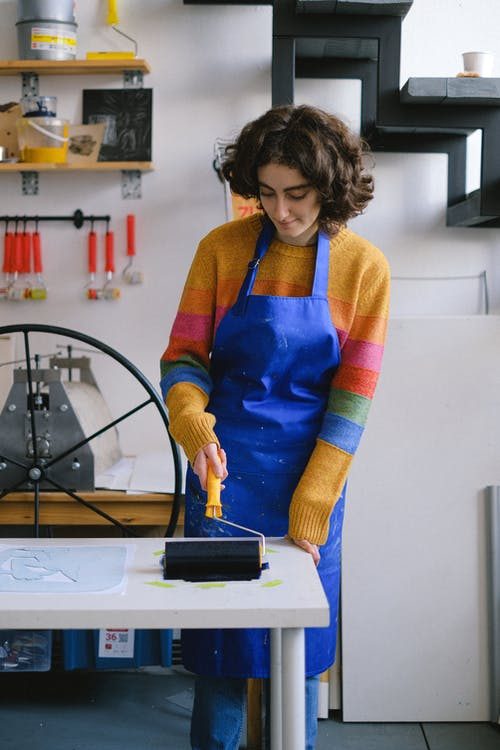 Painter with roller creating artwork on paper