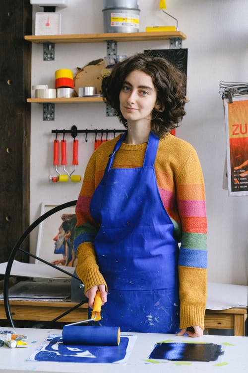 Young painter working in workshop with tools
