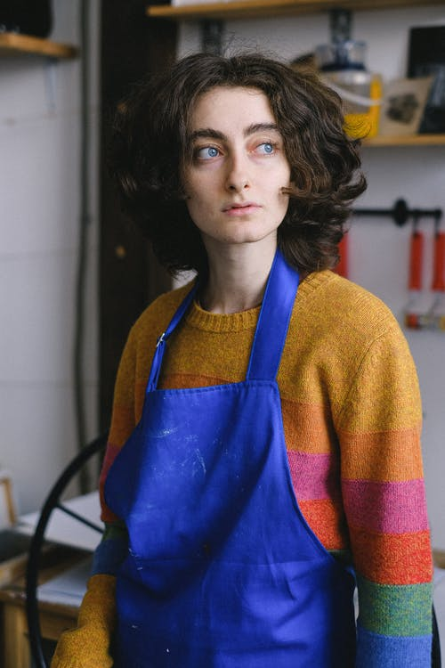 Young female artist in casual wear and blue apron thinking and looking away in arts craft shop