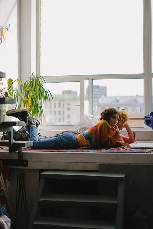 Side view of young designers lying on big windowsill and watching sketchbook in arts craft shop