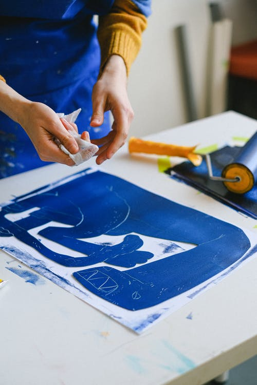 Unrecognizable female artist making stencil for creating etching picture on table in craft shop