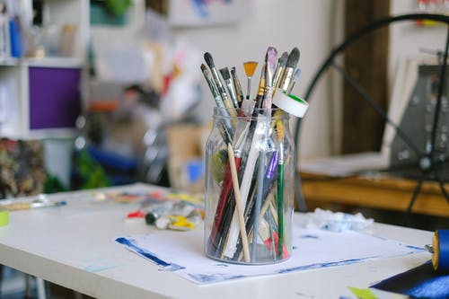 Glass jar with paintbrushes on desk with paint tubes in professional art workshop