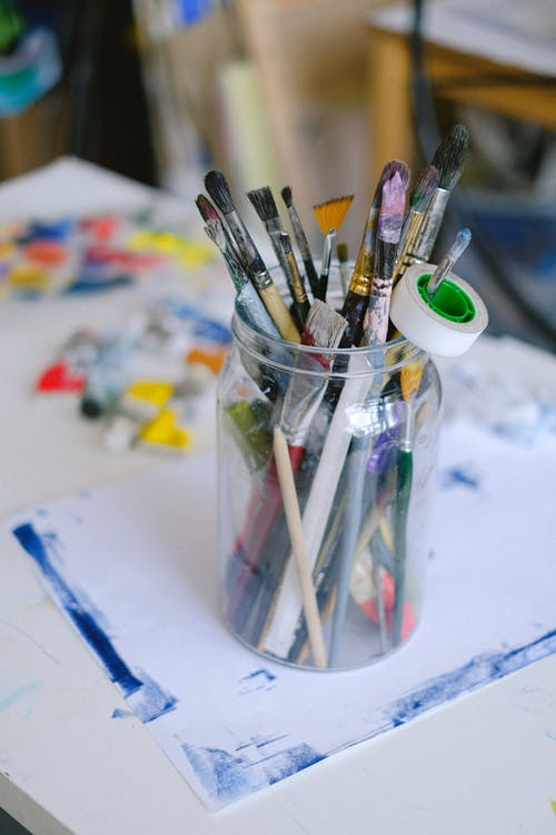 Assorted paintbrushes in jar on table in art studio